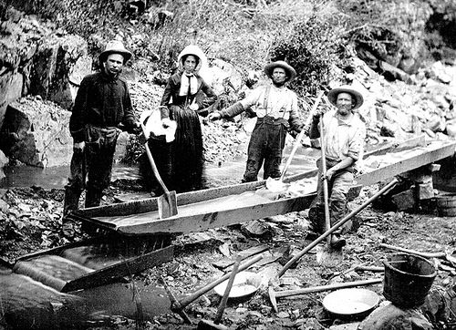 A Woman With Three Men Panning For Gold During The California Gold Rush